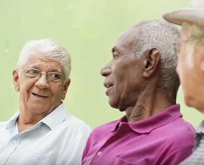 stock image of 3 elderly men chatting together on a bench