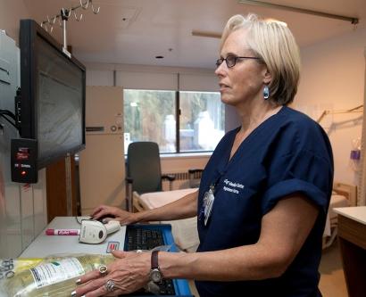 A nurse checks a patient's electronic medical record.