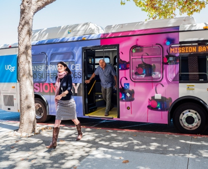 two people step off one of UCSF's new electric buses