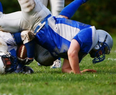 Two football players falling to the ground