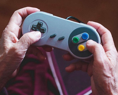 Elderly hands holding video game controller
