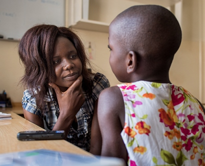 Betty Nyangoma talks with a child who was in the study about telling children they have HIV