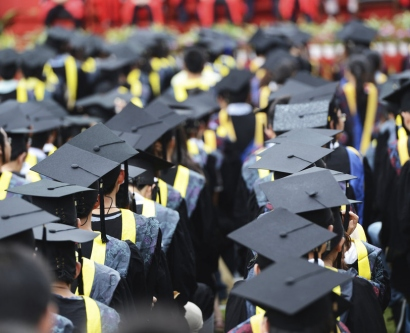 stock image of the tops of a crowd of student wearing their caps and gowns