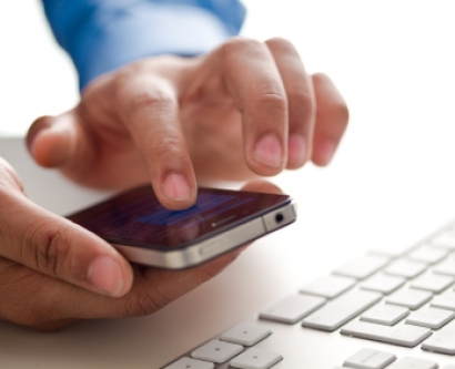 stock image of hands holding a smartphone next to a computer keyboard