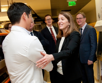 Sylvia Burwell shakes hands with a lab researcher at UCSF