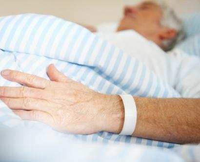 Stock photo of elderly patient in hospital bed