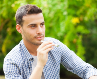 stock image of man holding an electronic cigarette in a park