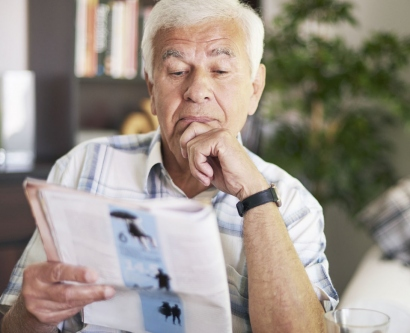 stock image of elderly man reading a magazine
