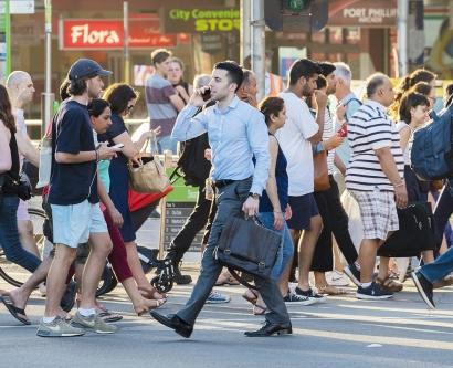 A man talks on a phone on a busy street