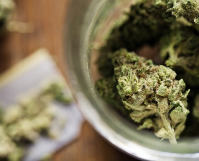 stock image of marijuana sitting in rolling paper and marijuana buds in a jar