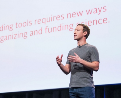 "Mark Zuckerberg on stage in front of a slide that says ""Building tools requires new ways of organizing and funding science."""