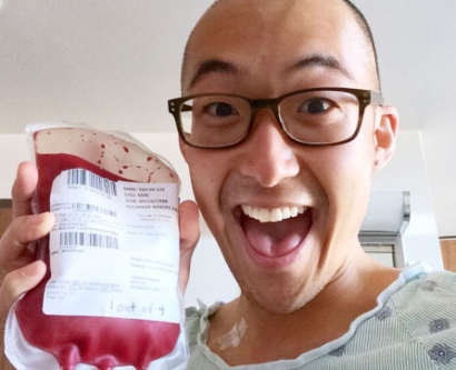Min Cho holds up his own blood bag in a selfie taken from his hospital room