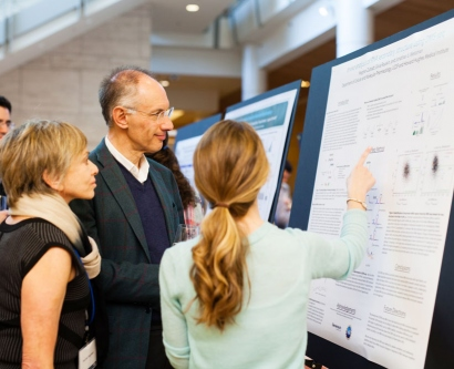 Sir Michael Moritz and Harriet Heyman discuss research with a fourth-year UCSF Discovery Fellow Meghan Zubradt