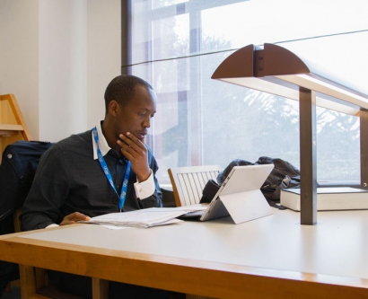 Theo Ndatimana studies at a table in the UCSF Library