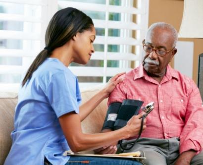 stock image of nurse taking an elderly man's blood pressure at home