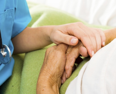 a nurse holds a patient's hand