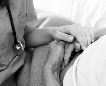 Stock image of nurse holding a patient's hand