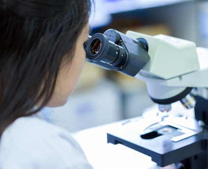 A stock image shows a female researchers looking into a microscope