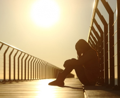 stock image of sad teen girl sitting on a bridge