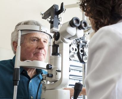 stock image of elderly man getting an eye exam