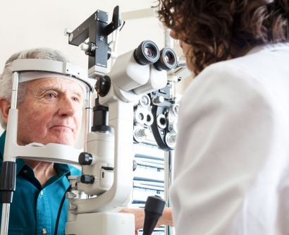stock image of an elderly man getting his eyes examined by a doctor