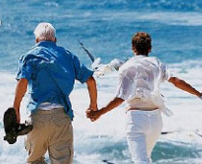 Image of a senior couple walking on the beach