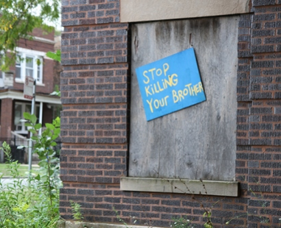 "Sign reading ""Stop Killing Your Brother"" on an abandoned home"