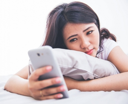stock image of sad woman looking at her smartphone