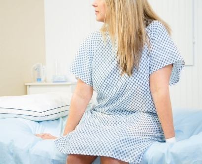 Stock image of a young woman sitting in a doctor's exam room