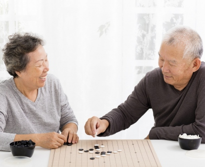 Elder couple playing a board game.