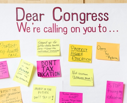 "a person walks past a whiteboard with the words ""Dear Congress We're calling on you to..."""