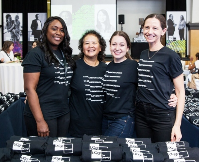 4 women pose for a photo at a table filled with UCSF Campaign t-shirts