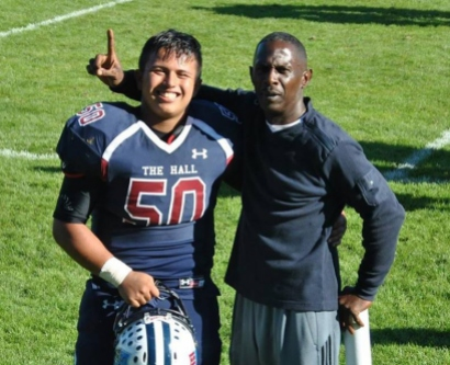Alexander Berbey, a student at Stuart Hall High School in San Francisco, stands on the football field with Noel Robinson, a football coach at Stuart Hall