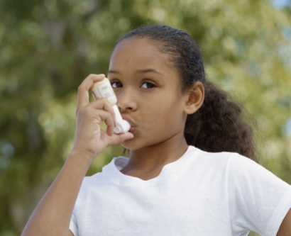 an African-American girl uses an asthma inhaler