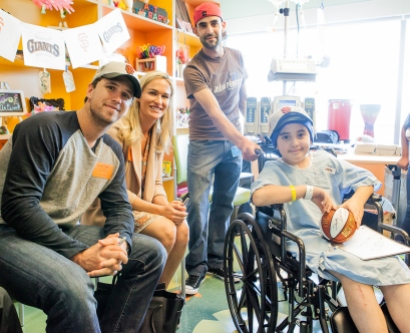 Buster Posey and Kristen Posey pose for a picture with a pediatric cancer patient during their visit to Benioff Children's Hospital San Francisco