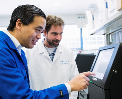2 scientists looking at a DNA sequencing machine