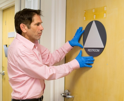 A worker installs new gender-inclusive restroom signage on a door