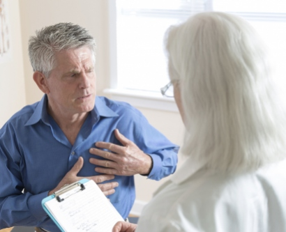 A stock image shows a man holding his chest while talking with a doctor