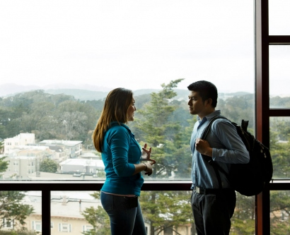 2 students talking in front of a picture window overlooking the Sunset district