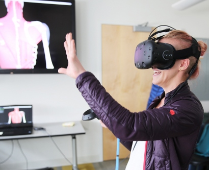 Carmen Marie Lee holds up her hands as she wears a virtual-reality headset
