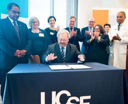 UCSF and ZSFG leaders stand behind Mayor Ed Lee as he signs legislation