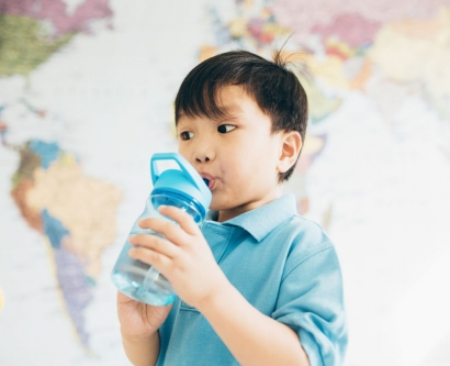 stock image of boy drinking from a water bottle at school