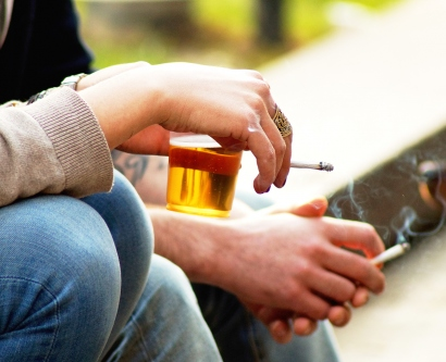 people smoke cigarettes while holding beer