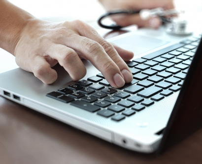 Doctor's hand typing on a laptop
