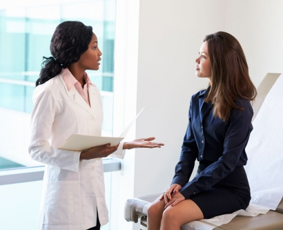 stock image of doctor talking to a female patient in an exam room