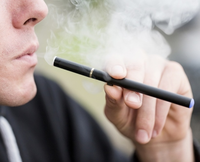 a man holds an e-cigarette