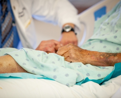 an elderly patient in a hospital bed with a doctor in the background