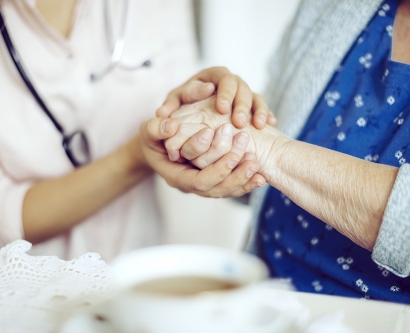 an elderly woman holds hands with a doctor