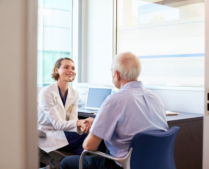 a female doctor talks with an elderly patient