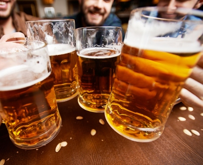 people hold glasses of beer
